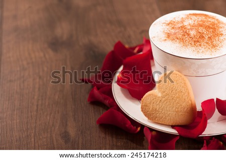 Lovely moment. Closeup image of heart shape cookie and cup of coffee placed with copy space on wooden table and decorated with rose petals - stock photo