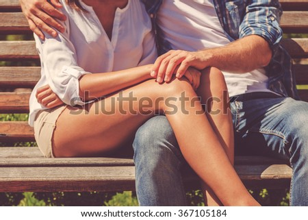 Lovely moments. Close-up of loving couple bonding to each other while sitting on the bench together - stock photo