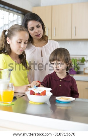 Lovely Mother and her children having breakfast in kitchen - stock photo