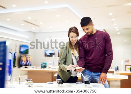 Lovely multiracial couple is at store and they are looking for a new mobile. Shallow depth of field. - stock photo