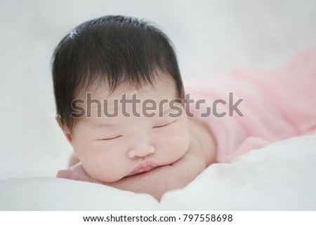 Lovely newborn Asian baby sleeping on furry cloth