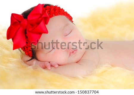Lovely newborn baby girl sleeping on  yellow fur and white background, wearing a red ribbon. - stock photo