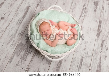 lovely newborn baby in hat and jumper sleeping in basket