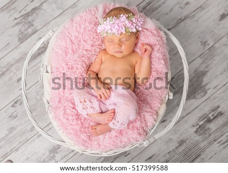 lovely newborn girl in pink panties and hat, with toy in basket on wooden background, top view
