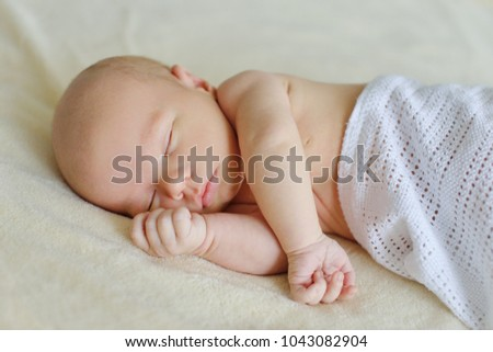 lovely newborn is sleeping on the bed
