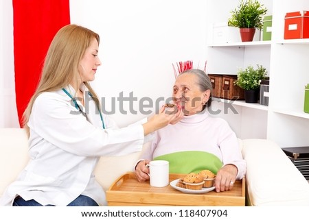 Lovely nurse helping old woman eating cookies - stock photo