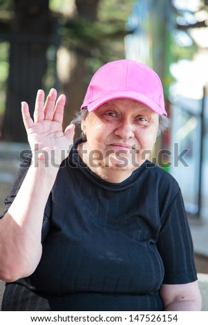 lovely old woman waving hand - stock photo