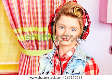 Lovely pin-up girl teenager listening to music in headphones on a pink kitchen. Beauty, youth fashion. Pin-up style. - stock photo