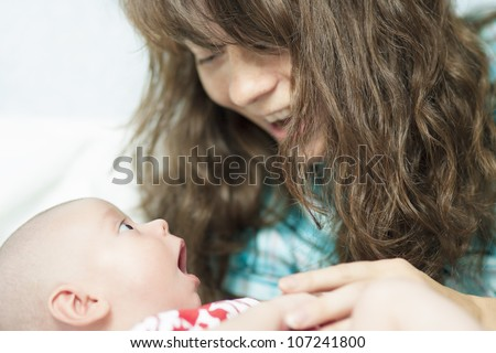 lovely portrait of a caucasian woman speaking to her son lying on cradle - stock photo