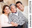 Lovely portrait of a grandmother with her family at home - stock photo