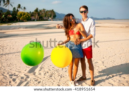Lovely Portrait of two happy young people dating and having fun on the beach.handsome man make surprise for his Girl,holding her man and  keeping color balloons in hand.Summer beach background.Outdoor - stock photo