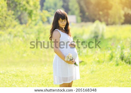 Lovely pregnant girl in white dress with wildflowers outdoors in sunny summer field - stock photo