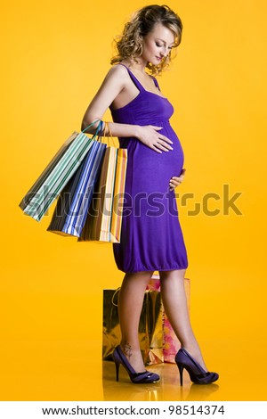 Lovely pregnant woman holding shopping bags over yellow background - stock photo