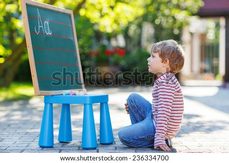 Lovely preschool boy at blackboard practicing writing letters, outdoor school or nursery - stock photo