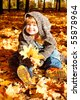 Lovely preschool girl sitting in an autumn park - stock photo
