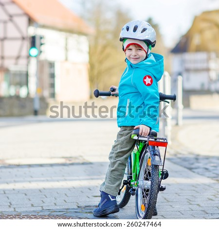 Lovely preschool kid boy in helmet riding with his first green bike in the city. Happy child in colorful clothes. Active leisure for kids outdoors. - stock photo