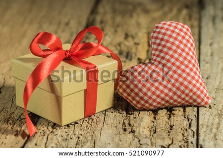 Lovely present with red bow and fabric heart on wooden table