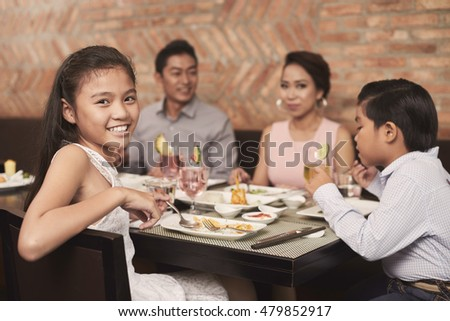 Lovely pretty girl sitting at dinner table and looking at camera