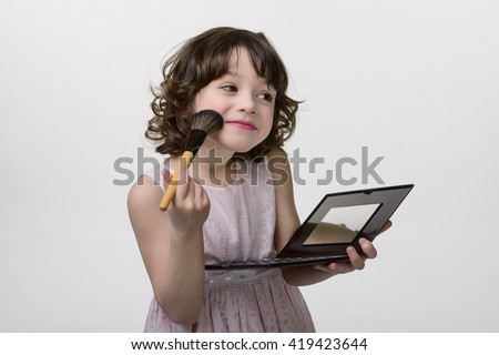 Lovely princess is applying the make up on her skin with special brush as she wants to look like her adult mother. Kid holds in her hands the palette with mirror. Gentle smile on childish face. - stock photo