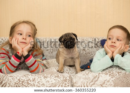 Lovely pug puppy and cute kids, watch TV - stock photo