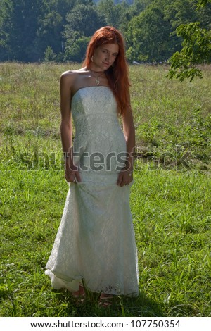 Lovely redhead woman standing outside in a green field, in her white wedding dress