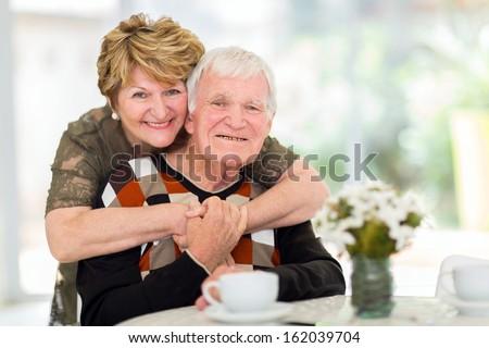 lovely retired elderly couple hugging at home - stock photo