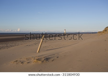 lovely sandy beach and distant lighthouse at talacre, north wales - stock photo