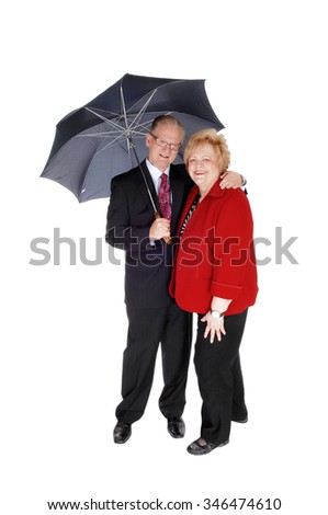 Lovely senior couple he in a suit and she in a red jacket standing with ablack umbrella, isolated for white background. - stock photo