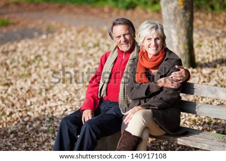 Lovely senior couple sitting on the bench in the park - stock photo