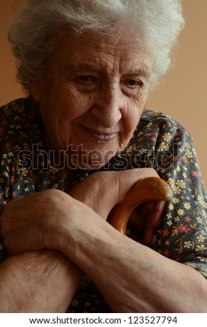 lovely senior woman holding wooden cane indoor  - stock photo