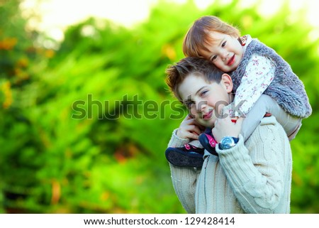 lovely siblings having fun outdoors - stock photo