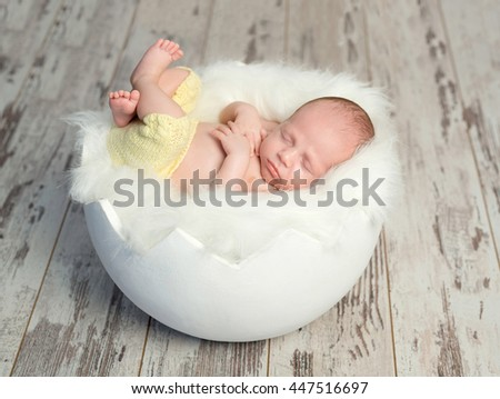 lovely sleeping baby in yellow pants with legs up on white cot like egg shell