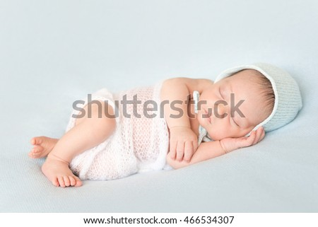 lovely sleeping covered newborn baby in hat on a blanket