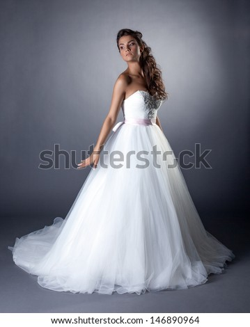 Lovely slim brunette posing in chic wedding dress - stock photo