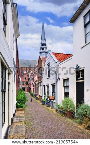 Lovely small alleyway with white plastered houses and a church on the background, Gouda, The Netherlands. - stock photo