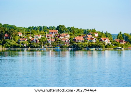 Lovely small, red cabins near the sea on an island full of green trees and shrubs. Houses climb up the hill towards the back letting them all have nice views from their homes. Calm water. Copyspace. - stock photo