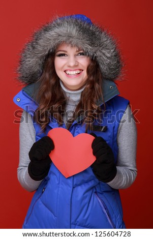 Lovely smiley caucasian woman wearing warm clothes with love symbol on St.Valentine Day background - stock photo