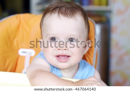 lovely smiling baby sits on baby chair in kitchen