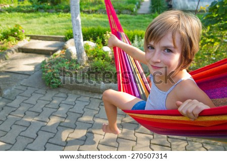Lovely smiling girl relaxing in a hammock - stock photo