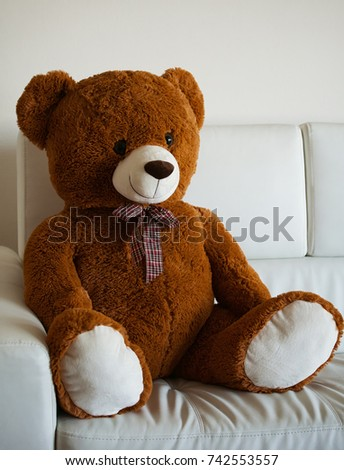 Lovely smiling vintage style teddy bear sitting on a white sofa.