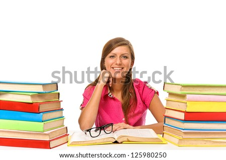 Lovely student is sitting on her desk with a stack of books, isolated on white