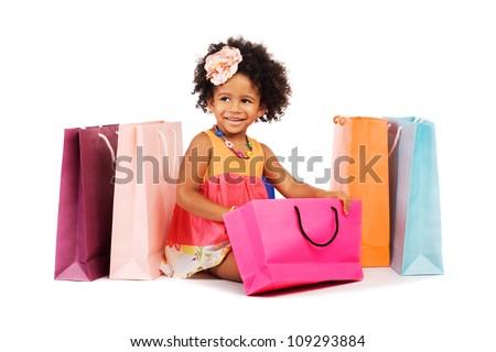 Lovely stylish little girl sitting among colorful shopping bags - stock photo