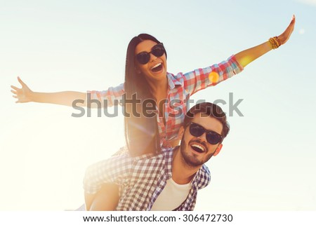 Lovely summer moments. Low angle view of cheerful young woman stretching out arms while sitting on the back of her boyfriend  - stock photo