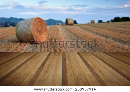 Lovely sunset golden hour landscape of hay bales in field in English countryside with wooden planks floor - stock photo