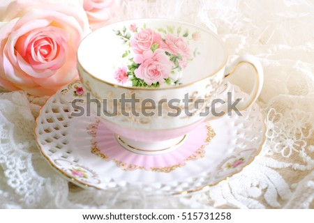 Lovely teacup on white table wiith pink rose