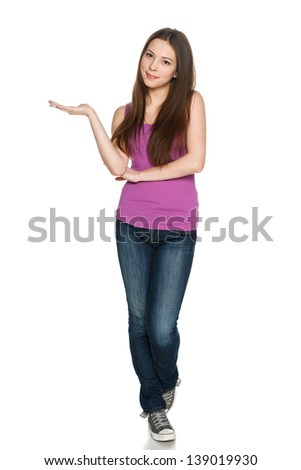 Lovely teen girl in full length standing casually and holding blank copy space at her palm, against white background - stock photo