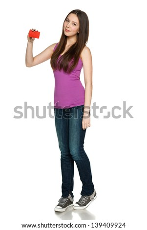 Lovely teen girl in full length standing casually and holding blank credit card, against white background - stock photo
