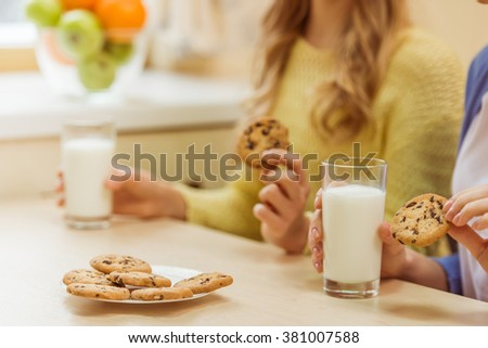 Lovely teenage girl and her beautiful mother eating cookies and drinking milk while sitting in the kitchen, close-up - stock photo