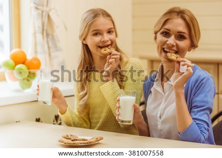 Lovely teenage girl and her beautiful mother eating cookies, drinking milk, looking at camera and smiling - stock photo