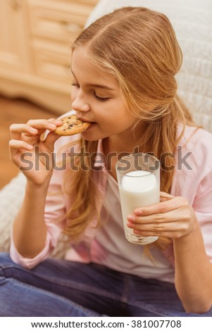 Lovely teenage girl holding a glass of milk and eating a cookie while sitting on the armchair - stock photo